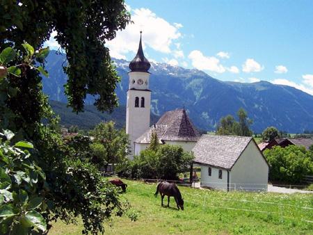 Kirche Wildermieming mit Blick auf die Stubaier Alpen.